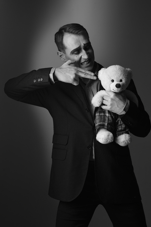 At gunpoint. Theatre and pantomime drama. Mime man pantomime shooting bear toy. Theatre actor with hand gesture killing teddy toy. Stage actor shooter with mime makeup, black and white Stock Photo