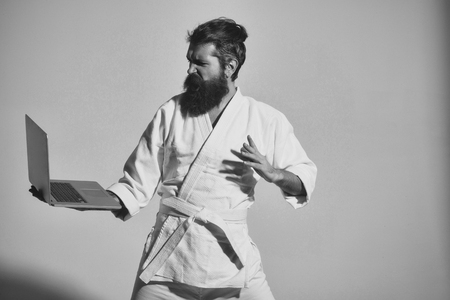 bearded angry karate man in kimono with laptop