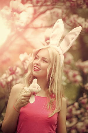 girl or cute woman with rosy, bunny ears hold magnolia Stock Photo