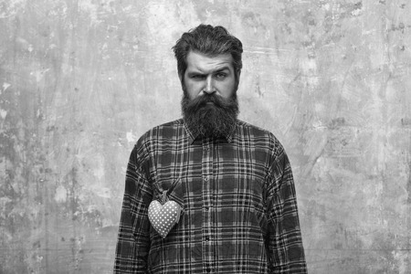 Bearded man with beard with rosy textile heart on shirt 스톡 콘텐츠