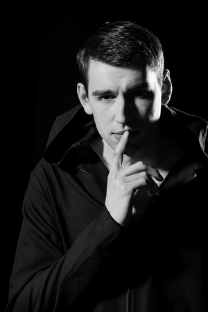 elegant man in stylish coat on black background, thoughtful face Stok Fotoğraf