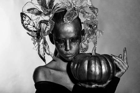 golden woman with halloween pumpkin Banque d'images - 114507498