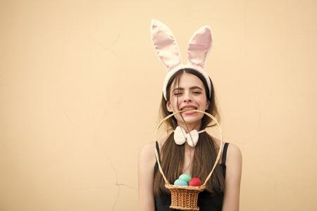 Easter girl holding wicker basket with eggs in teeth 版權商用圖片