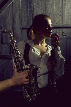 woman with microphone and man with sax