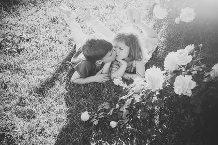 Boy kissing girl on green grass under rose bush 写真素材 - 114511961