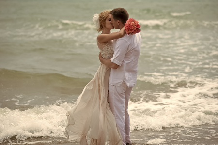 Kissing wedding couple on beach