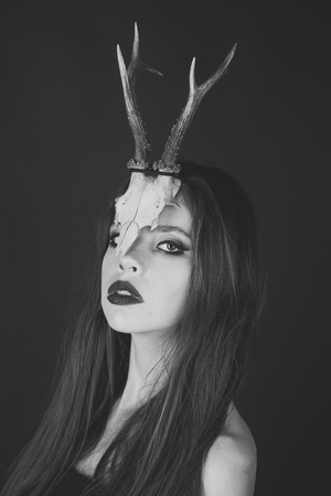 fashionable girl or woman with makeup and antlers. girl in strange skull antlers or horns.