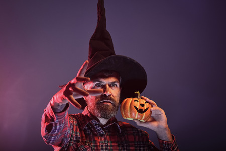 Halloween man in witch hat holding pumpkin in red light