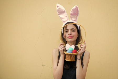 Easter woman with rosy bunny ears on beige background 版權商用圖片