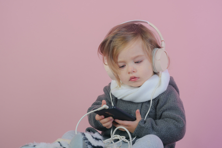 childhood and happiness. little girl child smiling. winter kid fashion. having fun. small happy girl. kid listen music with headset and mp3 on phone. Fresh funky beauty. Her perfect style. Banque d'images - 115009446