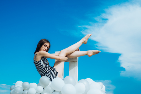 feeling freedom and dreaming. inspiration and imagination. girl sit in sky. Fashion portrait of woman. woman in summer dress with party balloons. sence of freedom.