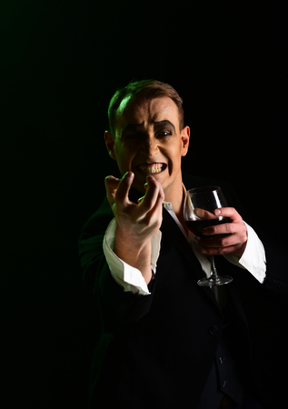 Hate. Comedian with mime makeup hold wine glass. Mime man. Mime artist perform on stage. Stage actor pantomime drinking wine. Drama theatre actor miming. Theatrical performance art and silen comedy.
