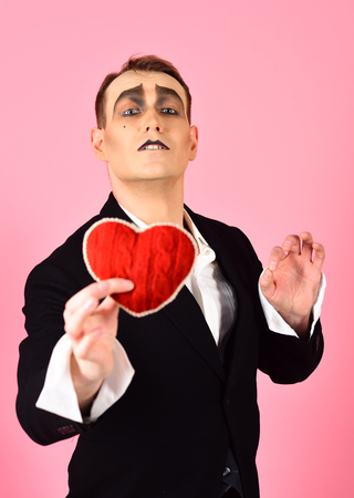 Serious about someone. Love confession on valentines day. Mime man hold red heart for valentines day. Mime actor with love symbol. Theatre actor pantomime falling in love.
