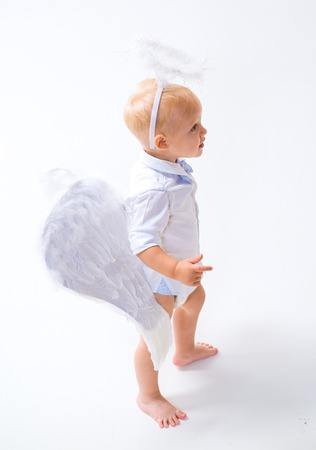 Waiting for wonder. Cute valentines cupid or cherub baby. Baby angel. Adorable little angel boy. Little boy with angel wings and halo. Christmas angel. Christmas party celebration. Banco de Imagens