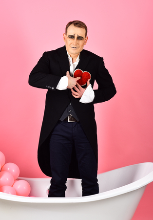 Happy valentines day. Mime actor has valentines celebration party. Mime man celebrate valentines day. Comedian actor hold red heart in bath. Being hopelessly in love performance. Stockfoto