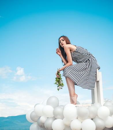 woman in summer dress with party balloons. inspiration and imagination. girl with flowers sit in sky. feeling freedom and dreaming. Fashion portrait of woman. Sexy beauty. Stock Photo