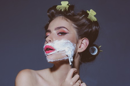 morning grooming and skincare. pinup girl with fashion hair. retro woman shaving with foam and razor blade. pin up woman with trendy makeup. pretty girl in vintage style. girl holding razor blade. Stok Fotoğraf