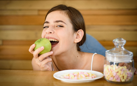Say no to unhealthy food. Woman choose what food to eat. Organic and natural or sweet and unhealthy. Vitamin or sugar. Dietetic or unhealthy food. Pretty woman prefer apple to marshmallows.