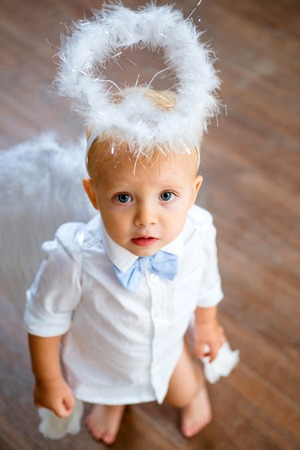 The fluttering of his wings. Baby angel. Christmas angel. Adorable little angel boy. Little boy with angel wings and halo. Cute valentines cupid or cherub baby. Christmas party celebration. Archivio Fotografico - 115009719