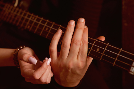 Sharing the rhythm of their life. Male and female hands play the electric guitar. Couple in love play duets. Couple of guitar players. Couple of musicians enjoy playing music. Instrumental music live