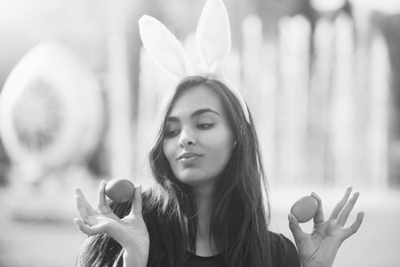 Cheerful girl with rosy bunny ears posing with colored eggs,