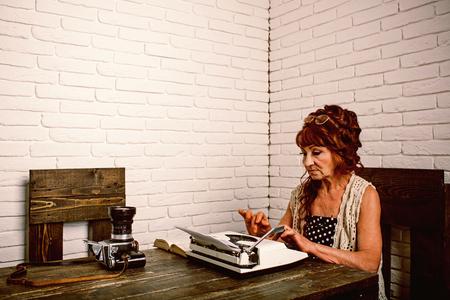 Old woman work in writer office. Senior woman type on retro typewriter. Journalist work in vintage office. Senior writer at desk. Female reporter or journalist writing on typewriter. Reklamní fotografie - 119121857