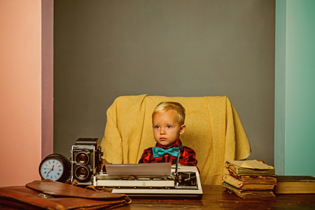 Little boy type research paper on typewriter. Child typewrite research work at desk.