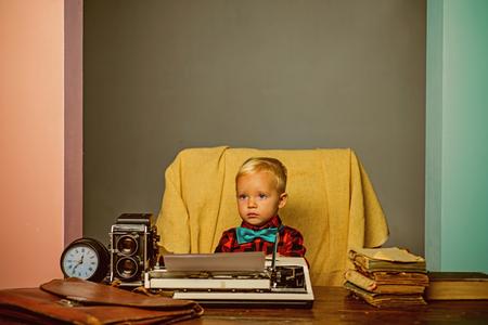 Little boy type research paper on typewriter. Child typewrite research work at desk.