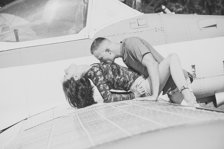 Couple in love full of desire  near airplane on background. Couple on excursion to museum of aviation in open air. Passion concept. Stock fotó