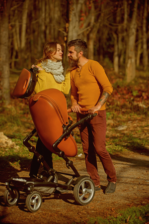 Family trust concept. Mother and father with baby pram enjoy sunny day in park, family trust. Road to life.