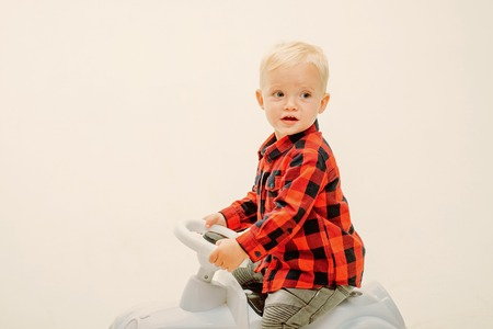 Little baby enjoy playing in kindergarten. Little child ride on toy car. Boy child on riding toy. Small toddler builds balance and motor skills. Child day care or nursery, copy space. Foto de archivo