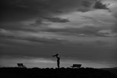 silhouette of father and child over dark sky with clouds and sea or ocean coast on evening or twilight on natural sunset background
