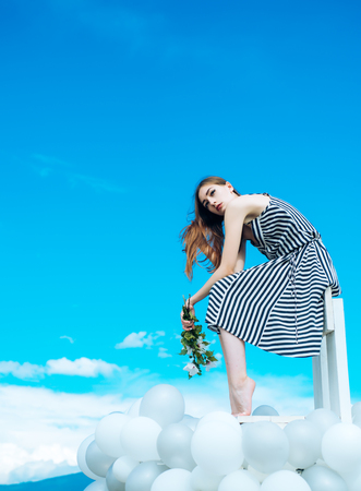 girl with flowers sit in sky. inspiration and imagination. feeling freedom and dreaming. Fashion portrait of woman. woman in summer dress with party balloons. Glamour fashion model. Stock Photo
