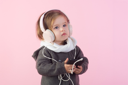 childhood and happiness. winter kid fashion. having fun. little girl child smiling. small happy girl. Feeling free and happy. kid listen music with headset and mp3 on phone. Autumn style. Stockfoto