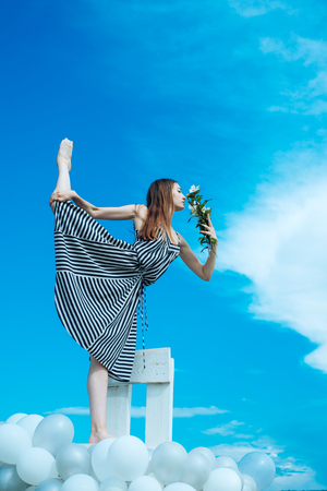 Fashion portrait of woman. girl with flowers sit in sky. feeling freedom and dreaming. inspiration and imagination. woman in summer dress with party balloons. acrobatics and sport. split Stockfoto