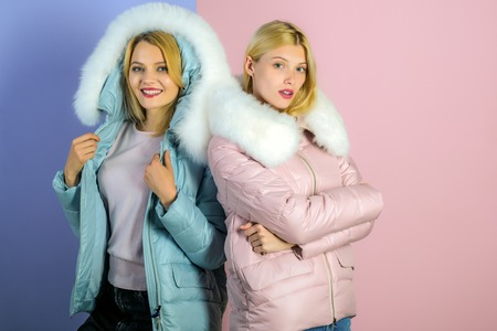 For a weather appropriate winter look. Pretty women in fashionable puffers. Sexy women wear warm winter coats. Fashion models in hoods with fur. Winter fashion trends. Keeps warm and looks good. Standard-Bild - 115010940