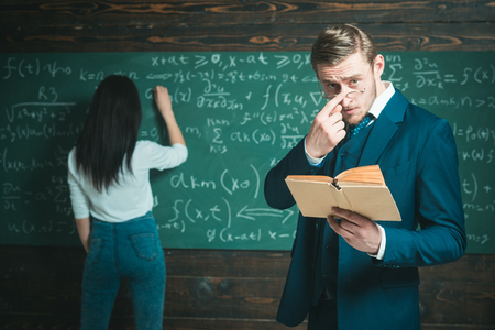 Learning math enables me to think clearly. Teacher man in glasses read problem statement from textbook to girl student. Rear view woman write equation on chalkboard. Doing sums. School day.