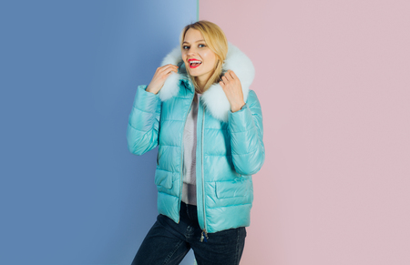 A look easily taken over winter. Fashion model in hood with fur. Pretty woman in fashionable puffer. Sexy woman wear warm winter coat. Winter fashion trends. Designed with cold weather in mind. 스톡 콘텐츠