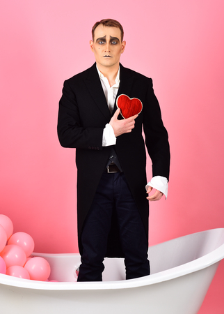 Blissfully in love pantomime. Mime actor has valentines celebration party. Comedian actor hold red heart in bath. Mime man celebrate valentines day. Happy valentines day. Love confession.