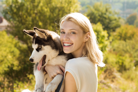 Canine companion. Happy dog owner play with family pet outdoor. Sexy woman with dog pet on summer day. Happy girl hold pedigree dog. This girl loves her siberian husky. Banco de Imagens
