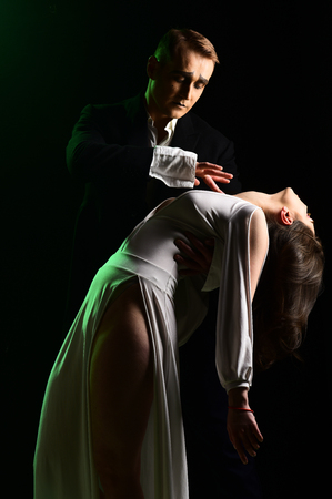 Falling in love. Mime man and woman act in romantic scene. Couple in love with mime makeup. Theatre actors miming through body motions. Couple of mime artists perform romance on stage. 스톡 콘텐츠