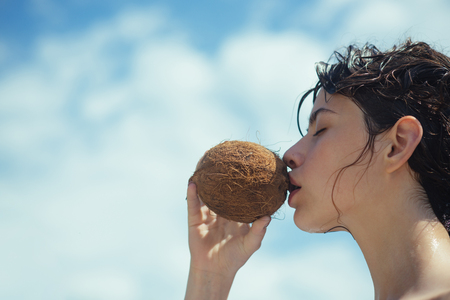 woman drinking coconut juice. summer vacation. coconut oil production. Clean eating diet, vegetarian and vegan. Woman is moisturizing her skin with a coconut cream. coco milk. drinking beach cocktail. Banco de Imagens