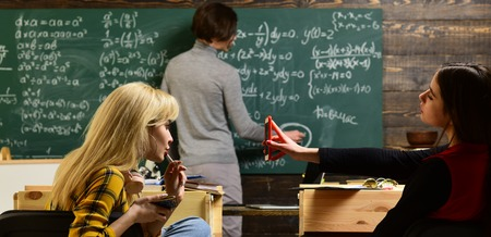 Teaching private classes is one of the best options for teacher now. Modern teacher hipster writing on big blackboard with math formula. Trying student is the one that has the most potential 写真素材