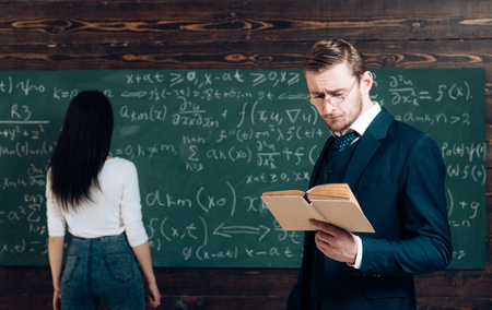 Working a problem in algebra. Doing sums. Teacher read book to girl student at chalkboard. Genius man and woman rear view in classroom. Education in university or home schooling. School day.