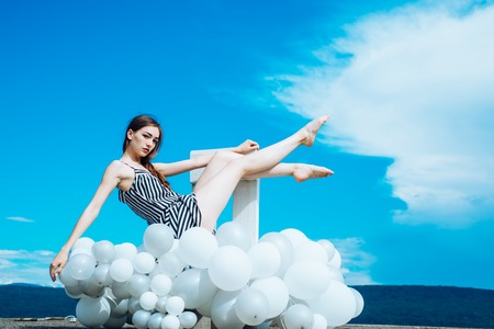 woman in summer dress with party balloons. Fashion portrait of woman. inspiration and imagination. girl sit in sky. feeling freedom and dreaming. Ambitious and beautiful.