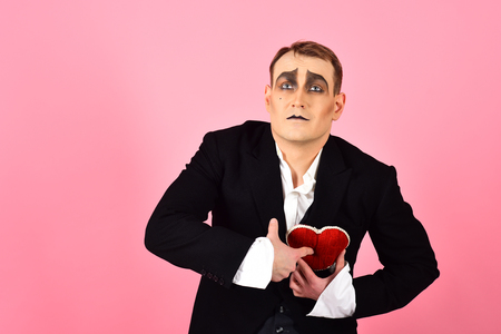 Act like being deep in love. Mime man celebrate valentines day. Mime actor has valentines celebration party. Comedian actor hold red heart. Love confession. Happy valentines day.