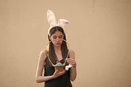 Easter woman holding wicker basket with colored eggs 版權商用圖片