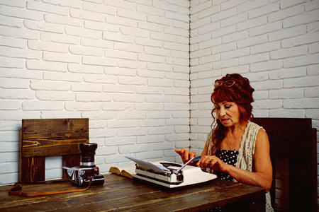 Final draft. Senior woman type on retro typewriter. Old woman work in writer office. Journalist work in vintage office. Senior writer at desk. Female reporter or journalist writing on typewriter
