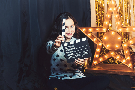 Happy child play with movie clapper or clapperboard. Little girl smile in film studio at golden star with light bulbs. Movie and film production. Imagination game and creativity concept