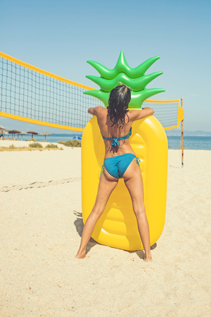 Summer image of stunning suntanned girl at yellow inflatable pineapple mattress on Volleyball Court Stockfoto - 115012094